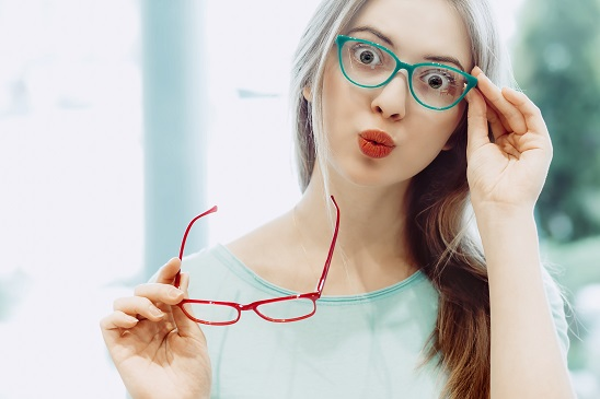 young woman with funny face trying on different pairs of eyeglasses - red and aquamarine